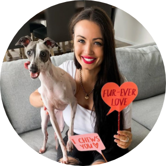 Woman sitting down with small dog under her arm and a heart shape sign in her hand.