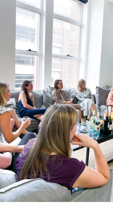 A group of women sitting on couches talking and drinking wine